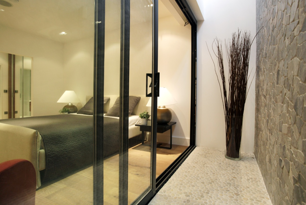 Basement bedroom with sliding doors leading onto light well