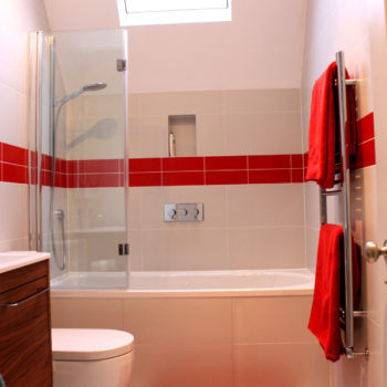 White bathroom suite with a strip of red tiles and accessories to add interest.